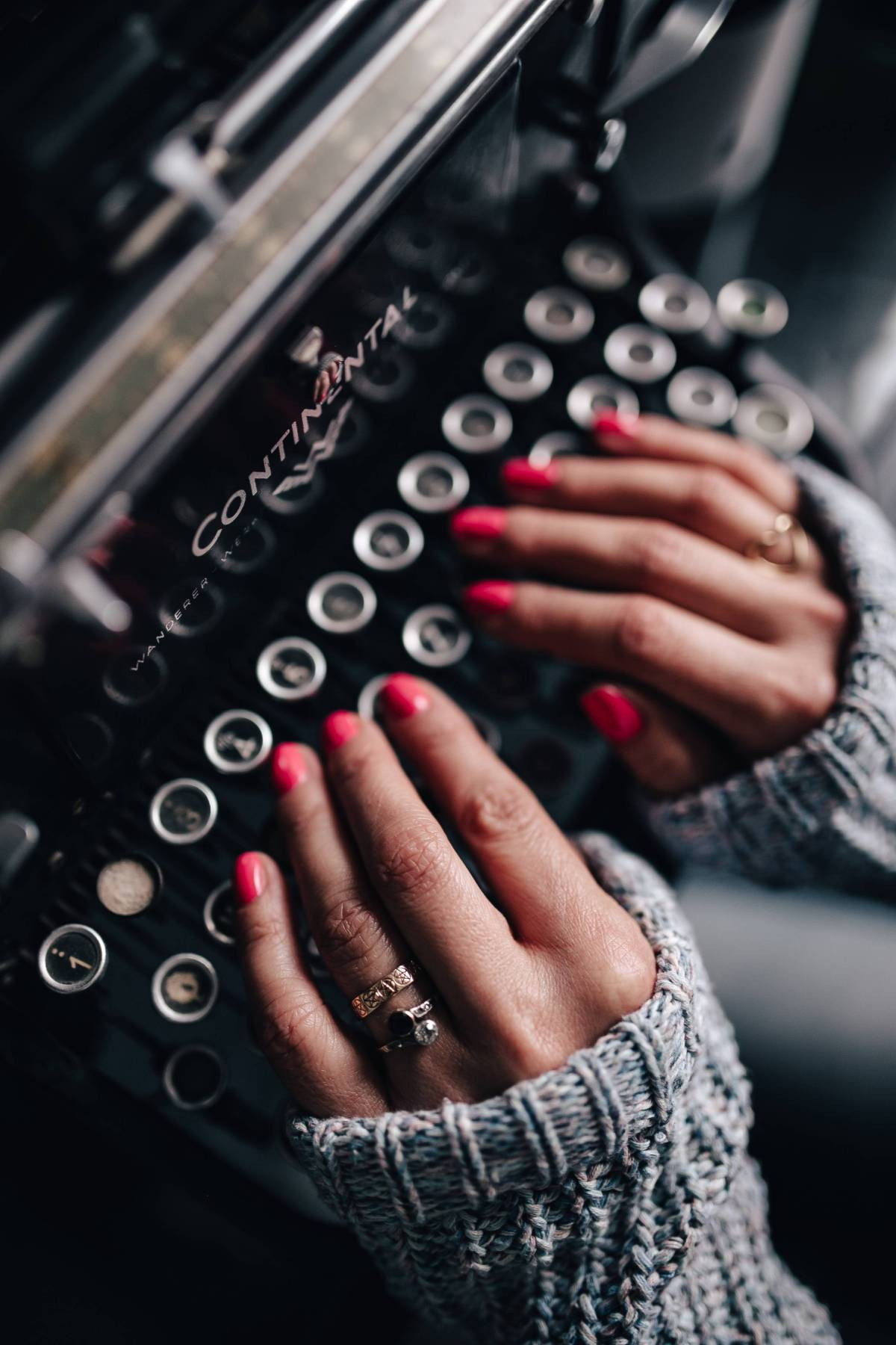 kaboompics_Woman typing on an old typewriter